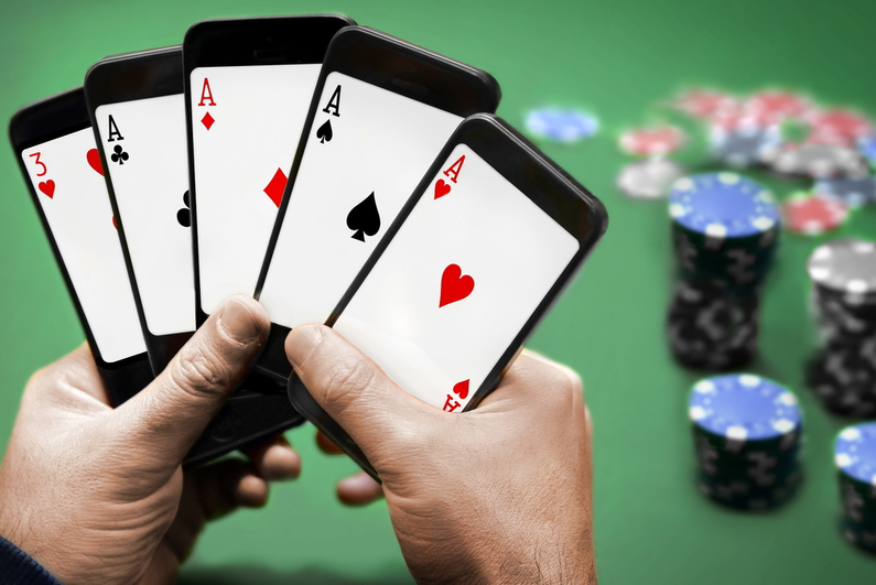Person playing poker, holding five smartphones like they are playing cards