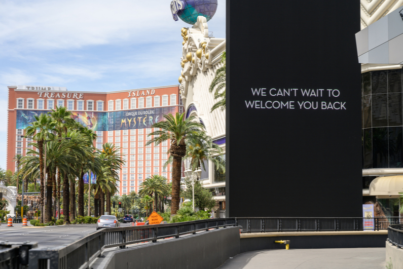 "Sign reading ""We can't wait to welcome you back"" on empty Las Vegas Strip with Treasure Island in background"