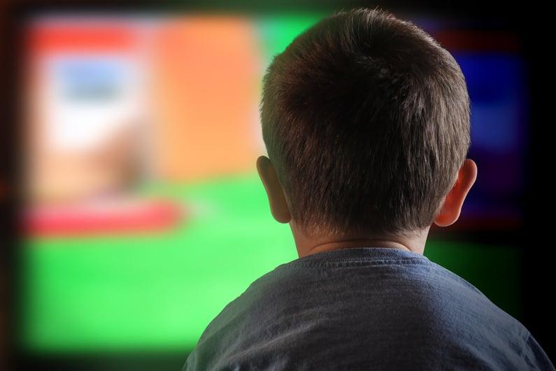 Bocah laki-laki menonton televisi