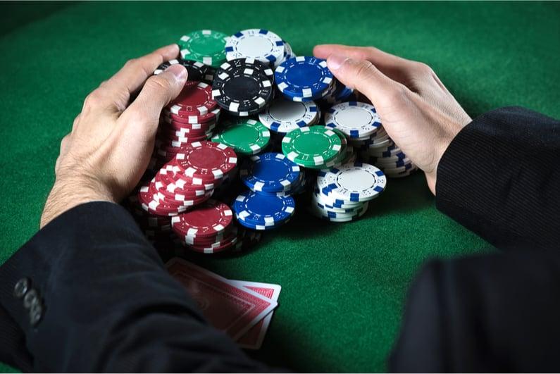 Man scooping large poker pot