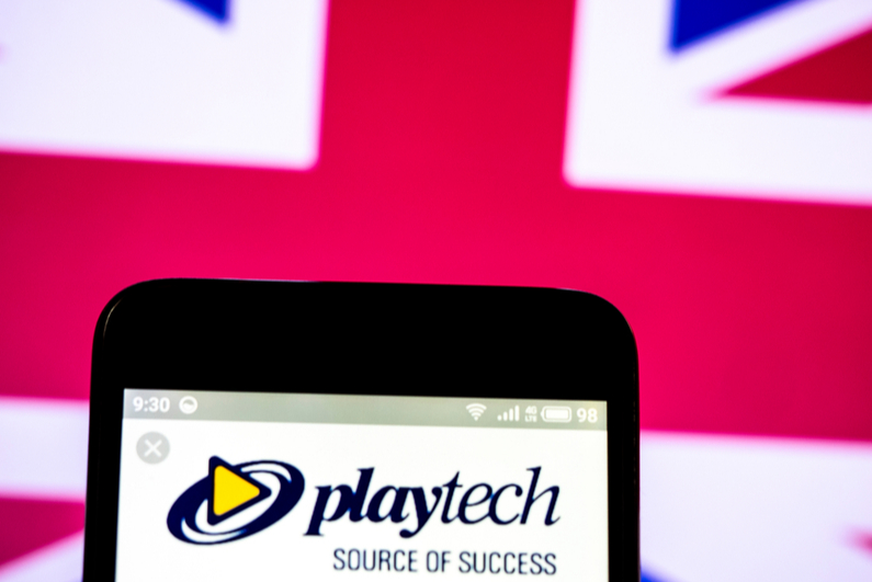 Playtech logo on a smartphone with UK flag in background