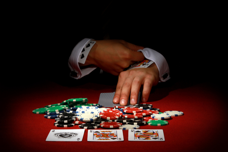Man with cards up his sleeve in poker game