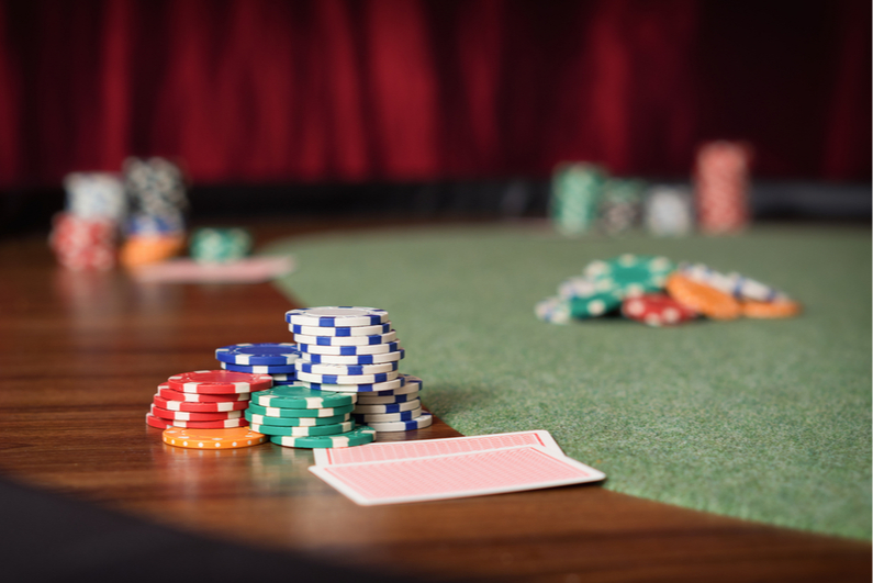 Table-level view of poker table with chip stacks and cards