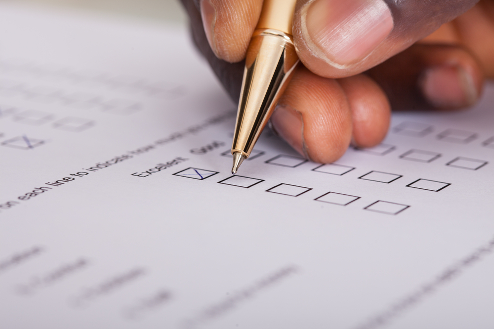 hand filling in questionnaire on paper