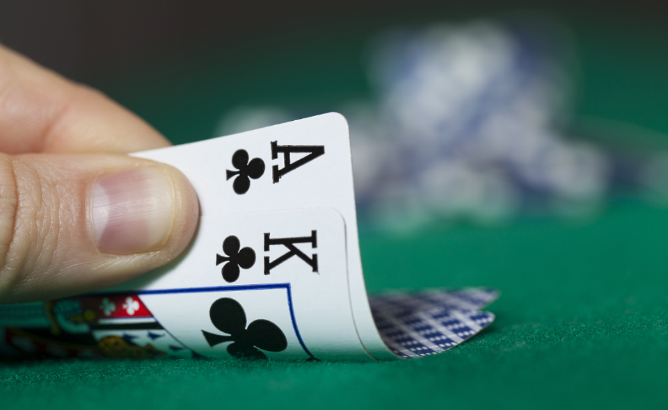 poker player peeking at A-K of clubs