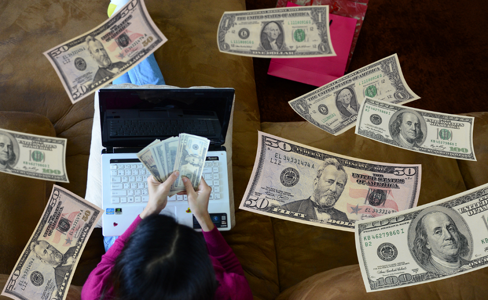 woman using laptop, holding cash, with cash floating down