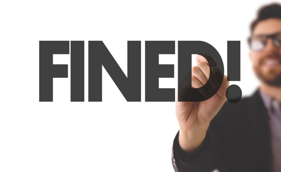 "male writing ""Fined!"""