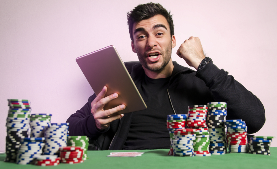 ecstatic man with tablet playing online poker