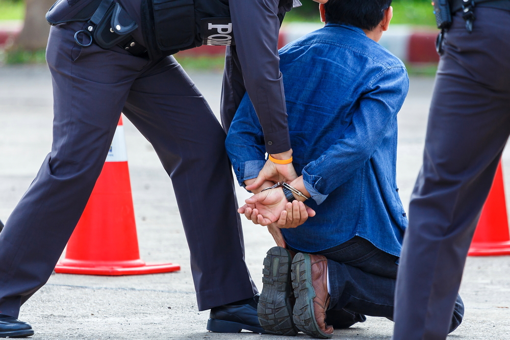 man being handcuffed by a police officer