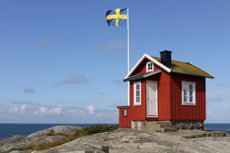Swedish flag flying over small shack next to the water