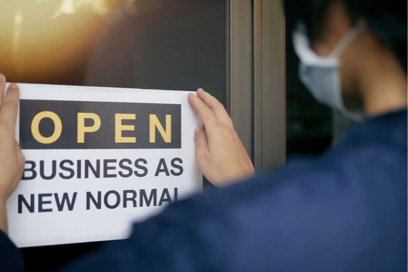 "Masked person putting sign in door that read, ""OPEN BUSINESS AS NEW NORMAL"""