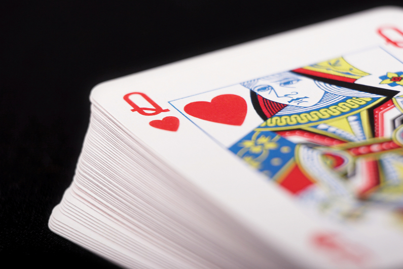 Deck of cards with Queen of hearts on top on black background