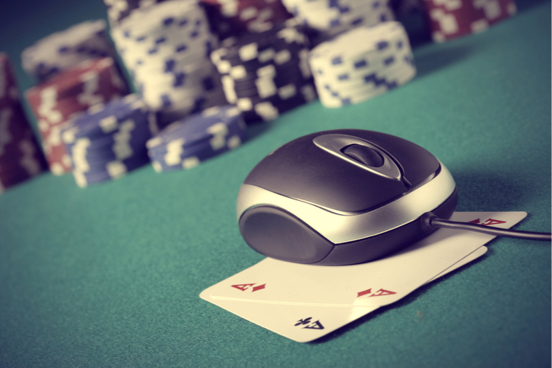 Computer mouse sitting on top of pocket Aces with poker chips in background