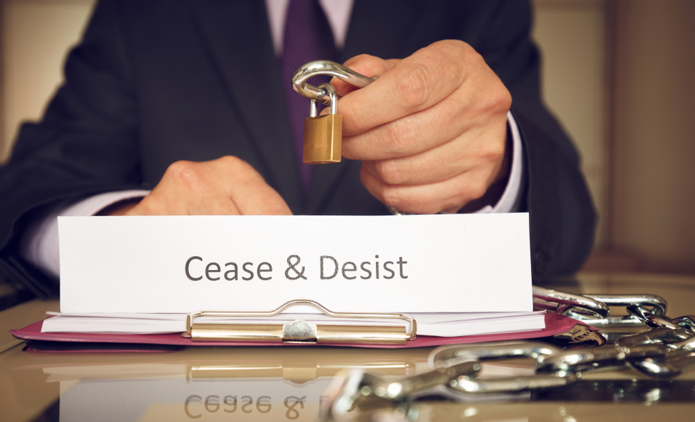 "main in suit holds lock and chain with ""cease and desist"" text on a paper in the foreground"