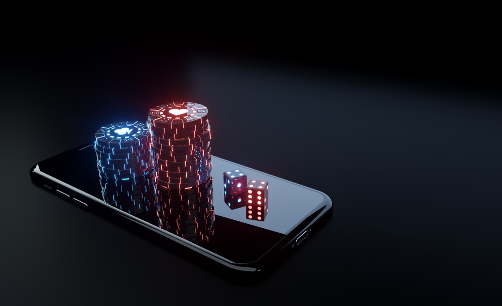 smartphone with red dice and blue and red casino chips on top