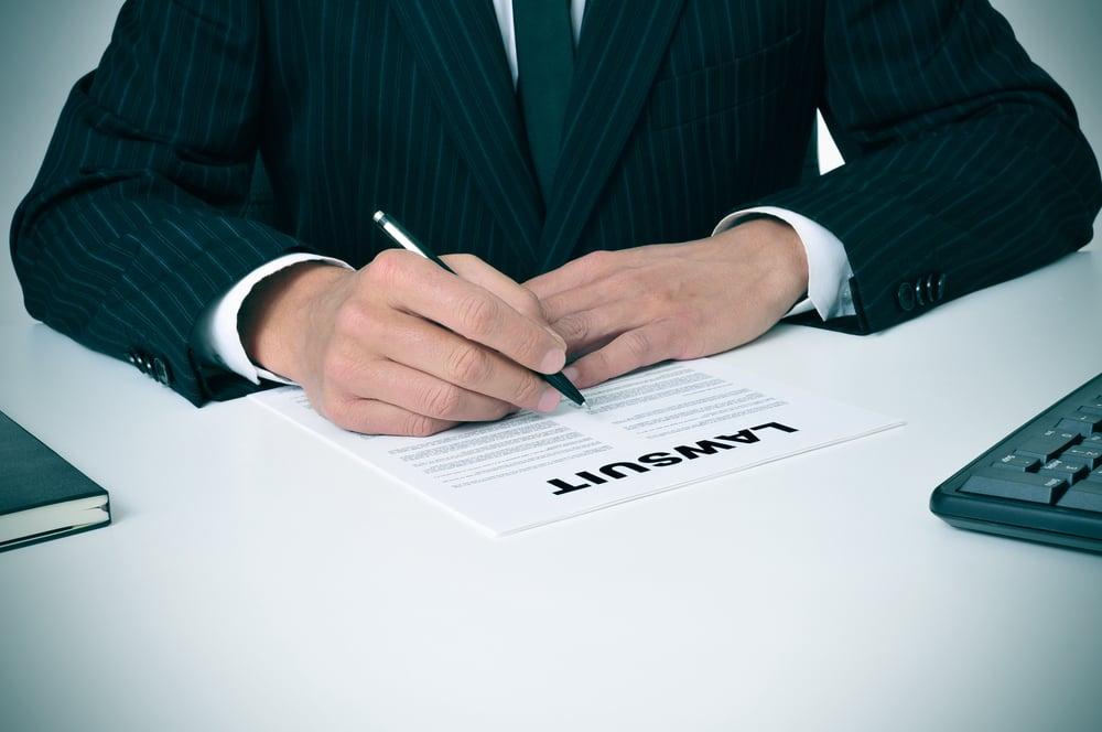 man in suit signing lawsuit paper