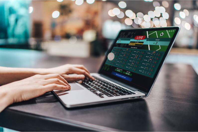 Person betting on sports on a laptop