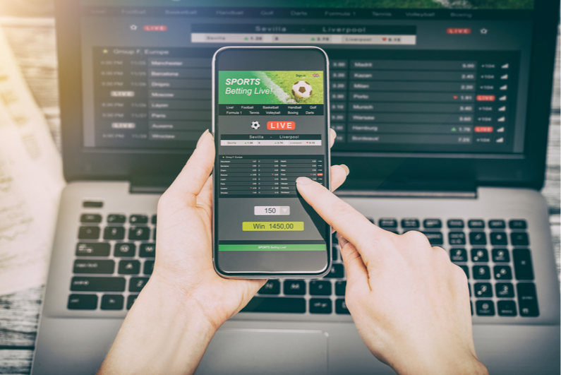 Person betting on sports on smartphone and laptop