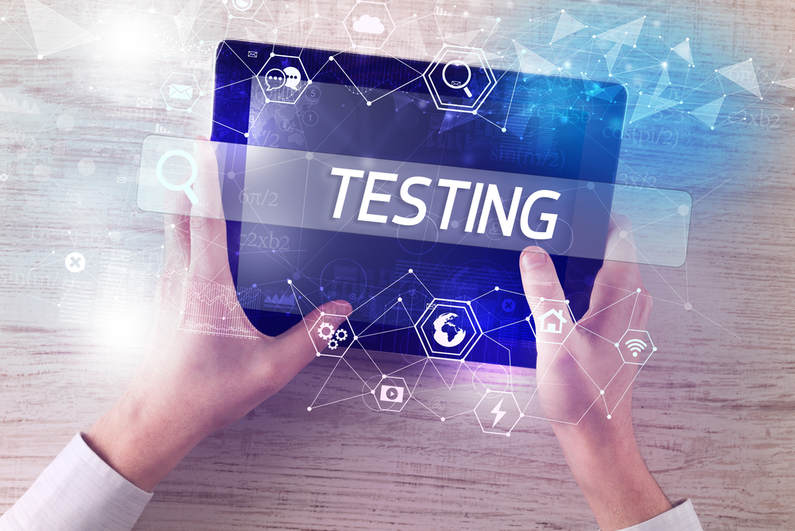 """Person holding tablet with """"TESTING"""" written above"""