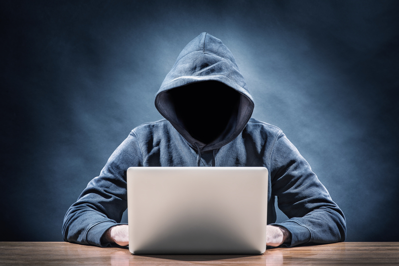 Faceless man in hoodie at a laptop