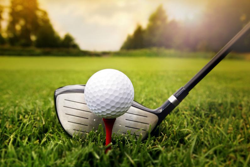 Golf club lining up a ball on a tee