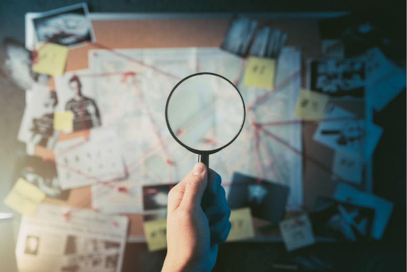 Magnifying glass looking at investigation board