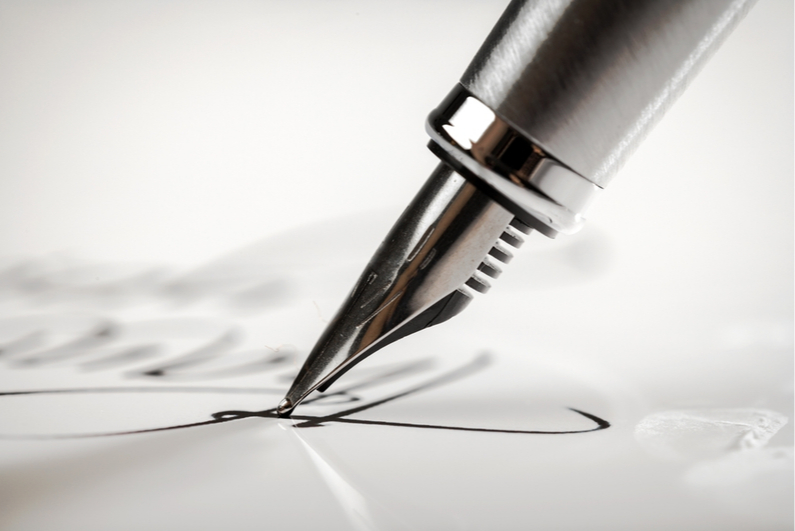 Pen signing a document