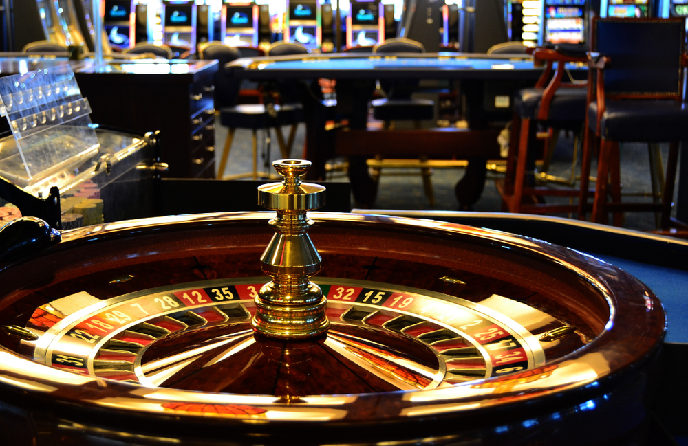 roulette wheel and table at casino facility with slot machines in the background