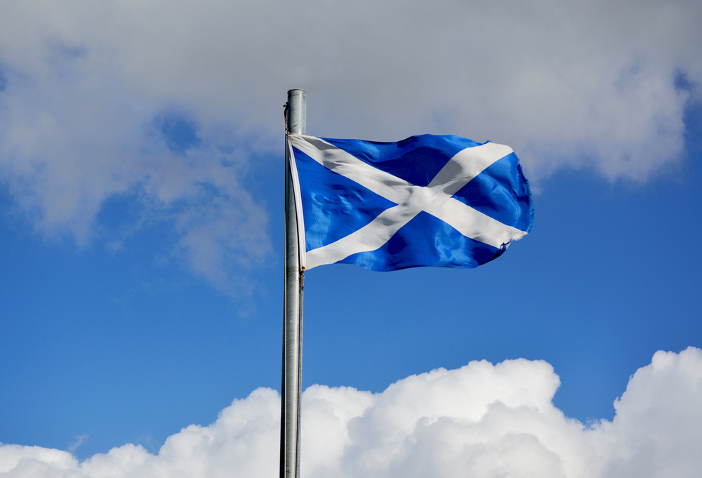 flag of Scotland against bright blue sky background