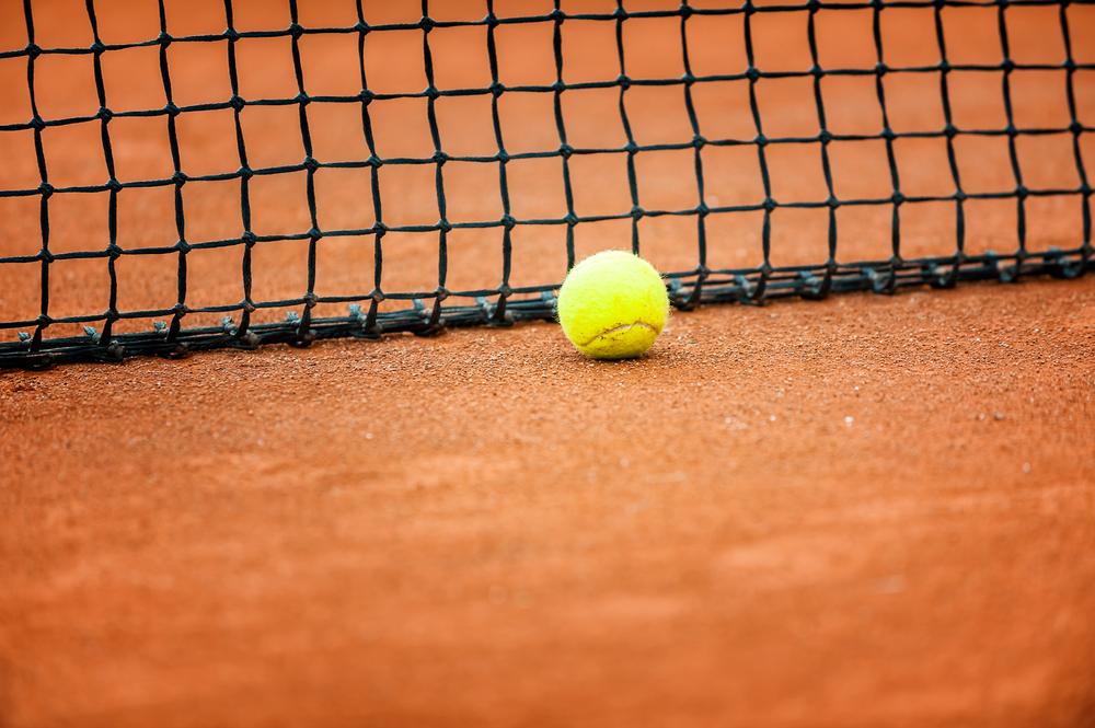tennis ball near the net on a court