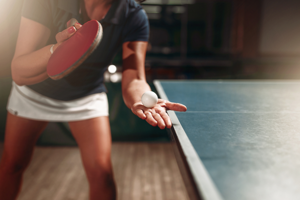 female table tennis player holding ball and racket