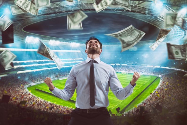 man rejoices in a stadium as cash falls from the sky