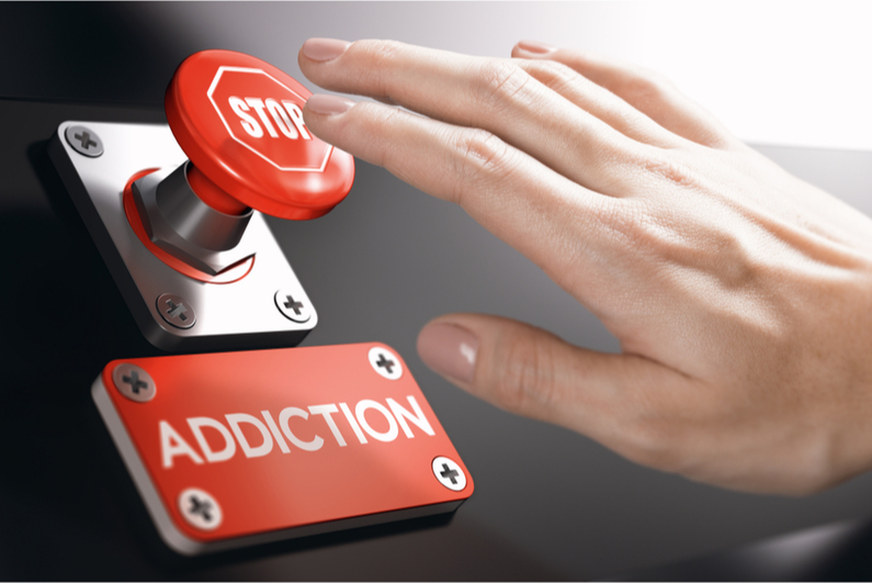 person pressing stop button above addiction sign