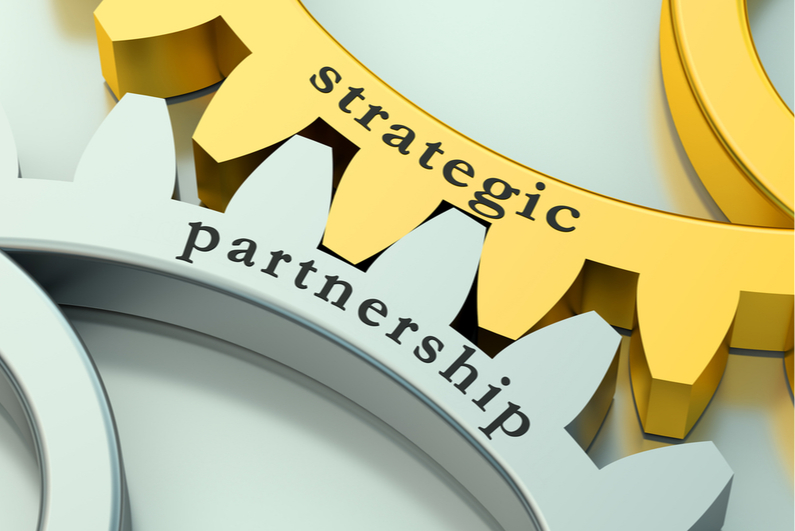 """Two interlocked gears labeled """"strategic"""" and """"partnership"""""""