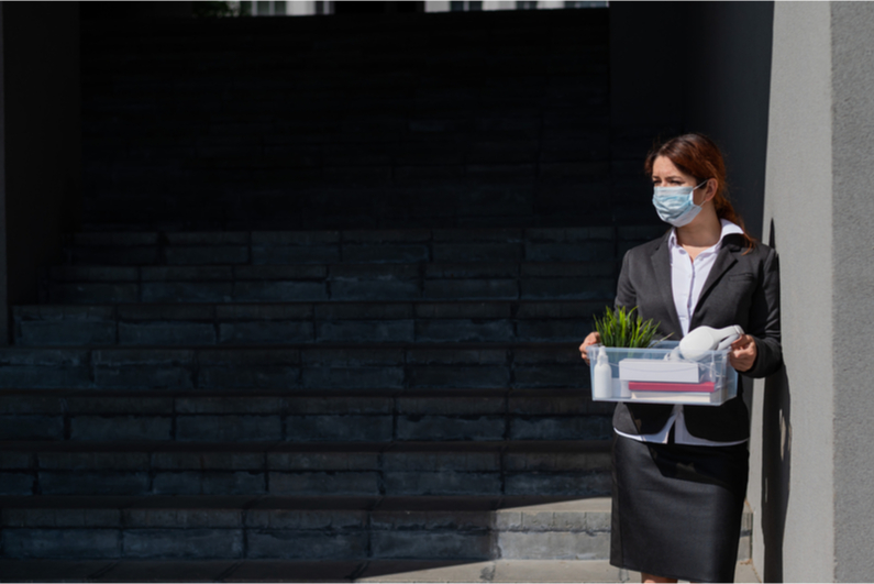 Business woman in mask holding belongings after being laid off