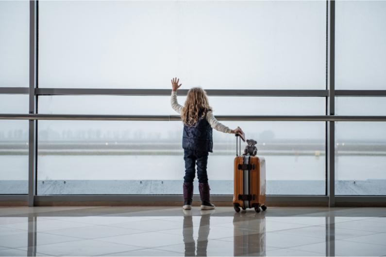 Child waving goodbye to plane at airport