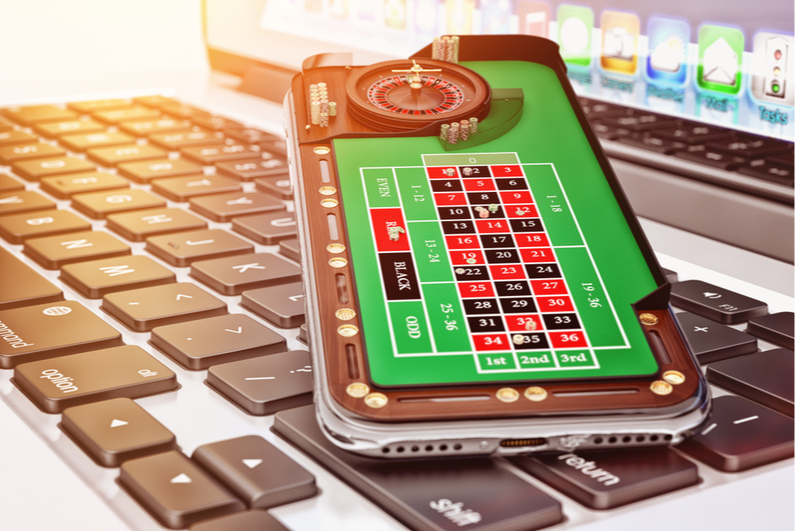 Artistic rending of a smartphone with a mobile casino app sitting on a laptop keyboard