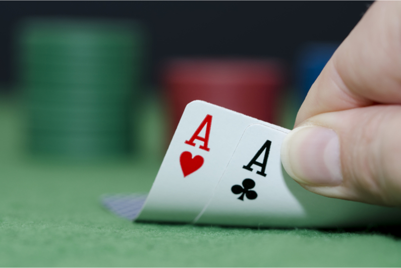 Poker player with pocket aces as hole cards