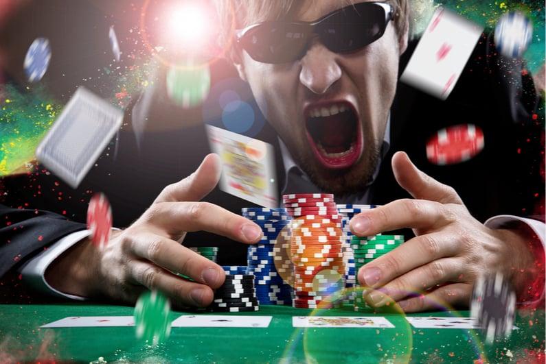 Excited man winning a big poker pot