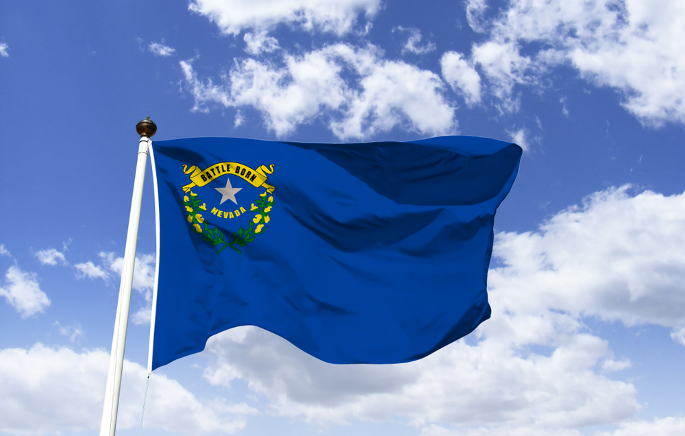 flag of Nevada state against blue sky and clouds background
