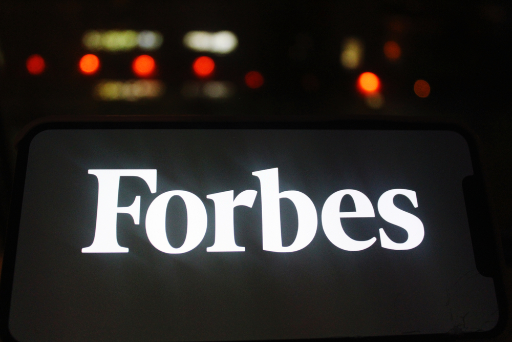 white Forbes logo displayed against a black background on a digital screen