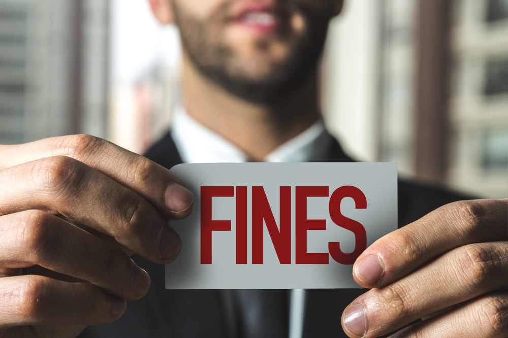 """man in suit holding up card reading """"fines"""""""