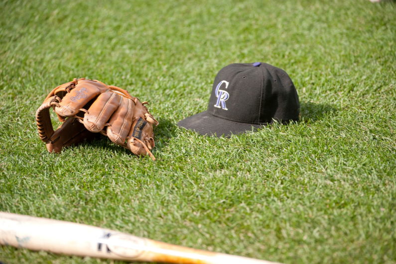 Colorado Rockies baseball cap and bat on the grass