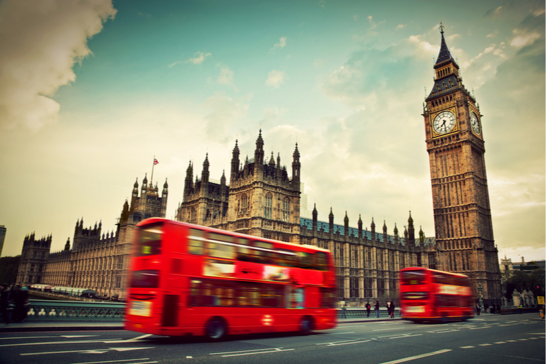 Red double-decker buses driving past Big Ben in London