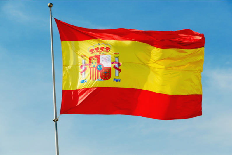 Spain's flag flying against a blue sky background