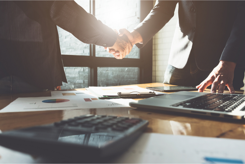 Two businesspeople shake hands over a conference table