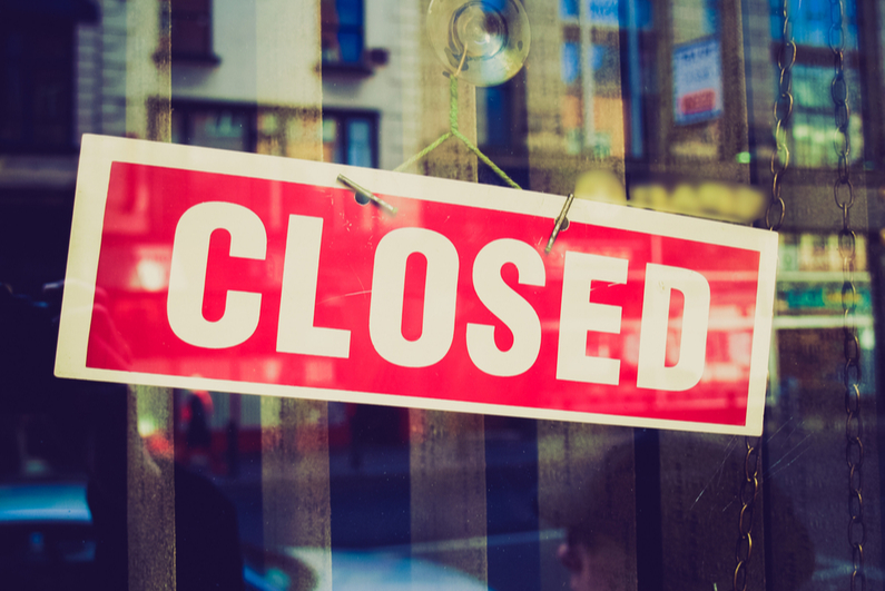 Closed sign hanging in store window