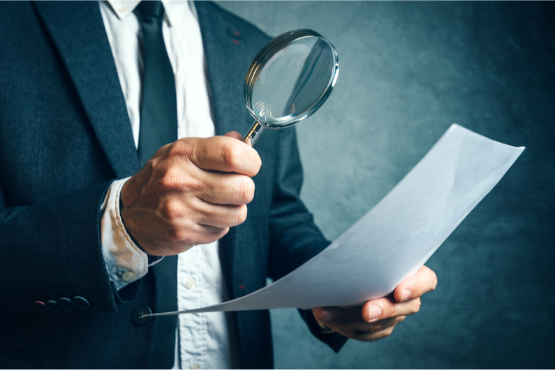 Man examining a piece of paper with a magnifying glass