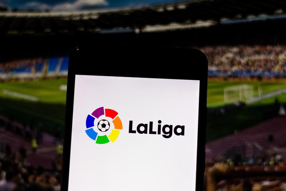 LaLiga logo on smartphone against soccer match background