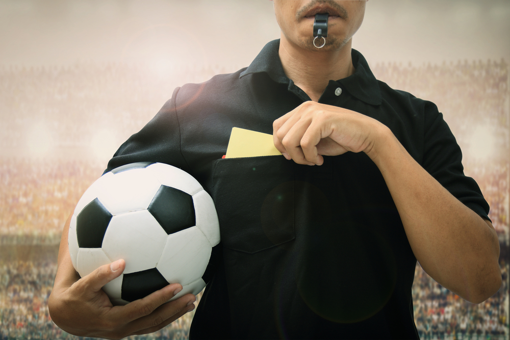 moustached soccer referee blows whistle while holding ball and yellow card